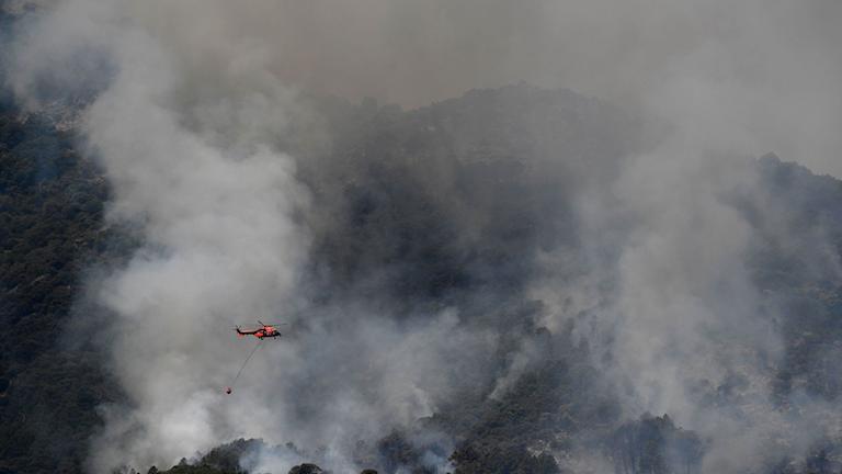 Helikopter försöker vattenbomba en skogsbrand i centrala Spanien.