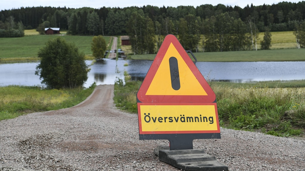 Varningsskylt för översvämning på väg i förgrunden, översvämmad väg i bakgrunden.