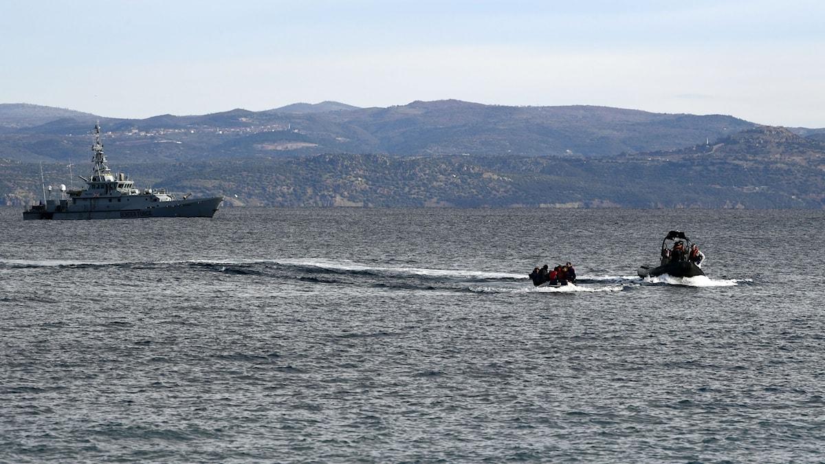 Flyktingar och migranter i gummibåtar möts upp an Frontex fartyg utanför Lesbos, Grekland.