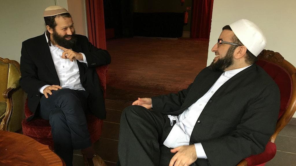 Bilden visar rabbinen Moshe-David HaCohen som sitter och pratar med imamen Salahuddin Barakat. Bägge männen bär vit skjorta och mörk kostym, med judisk respektive muslimsk huvudbonad. Foto: Anna Landelius/Sveriges Radio.