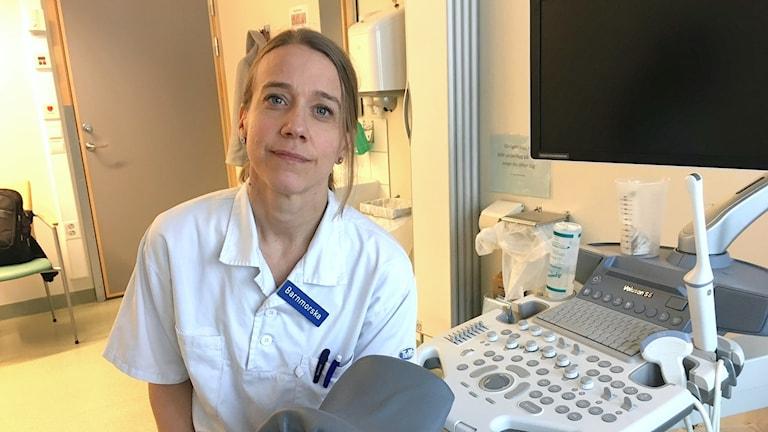 Helena Kilander i vit rock på ett besöksrum, i bakgrunden en ultraljudsapparat.