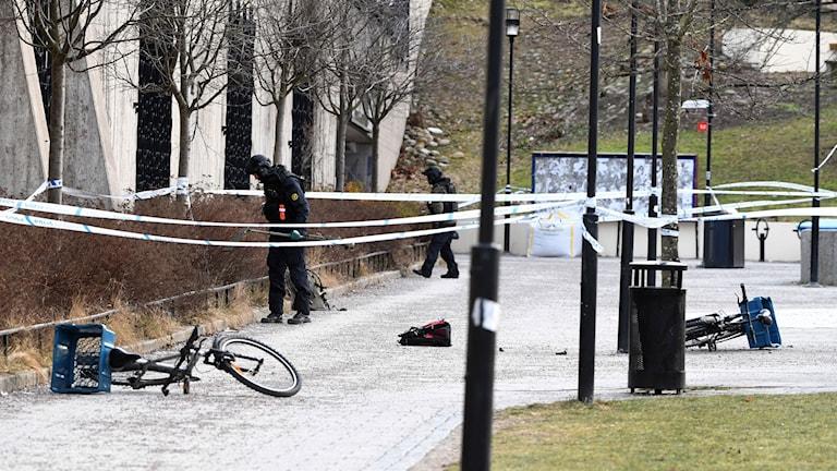 Bombtekniker på plats inom det avspärrade området. Två cyklar och en väska ligger på marken.