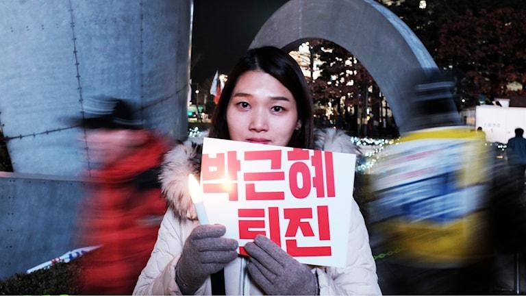 """""""Avgå, Park Geun-hye"""", står det på skylten som Jung Hyun-soo bär. Protesterna tycks inte mattas efter presidentens tal idag med ett halvt löfte om avgång."""