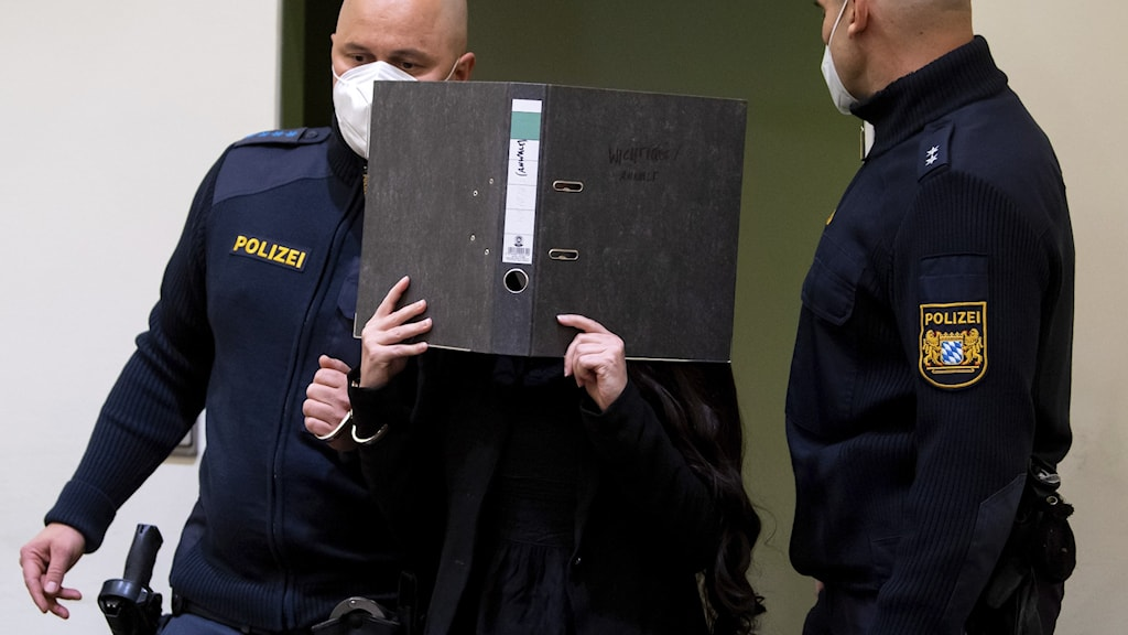 En kvinna står mellan två poliser och håller upp en pärm framför ansiktet