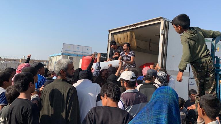 En folkmassa står och tar emot isblock för att kunna kyla mat i Al Hol-lägret i norra Syrien.
