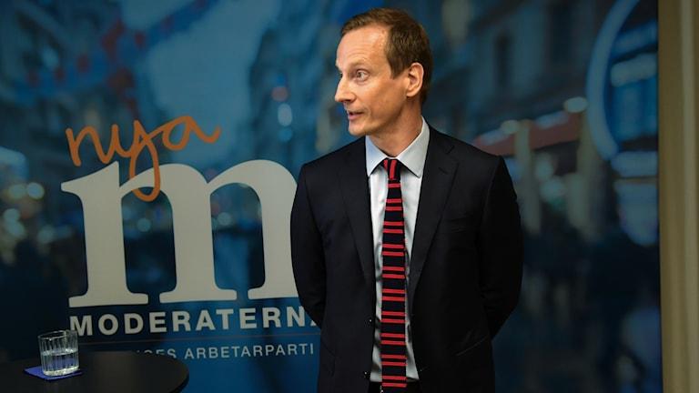 Anders Edholm står framför en vägg där det står Nya Moderaterna