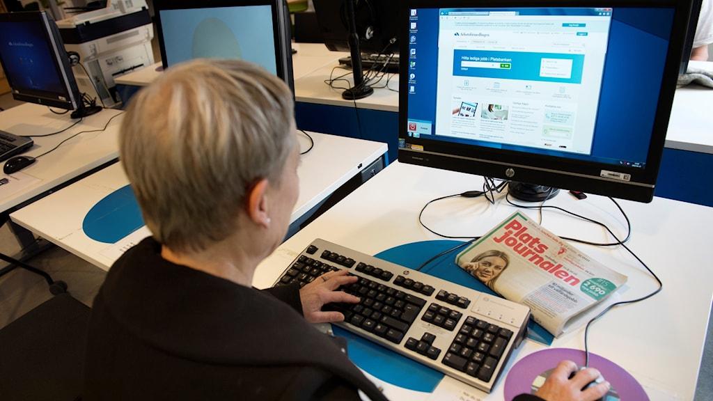 Arbetslös kvinna vid en dator på Arbetsförmedlingen.