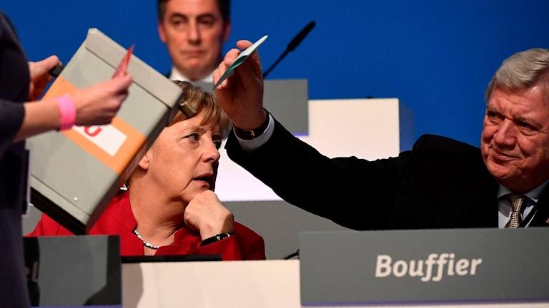 Man som stoppar röstsedel i valurna med Merkel i bakgrunden