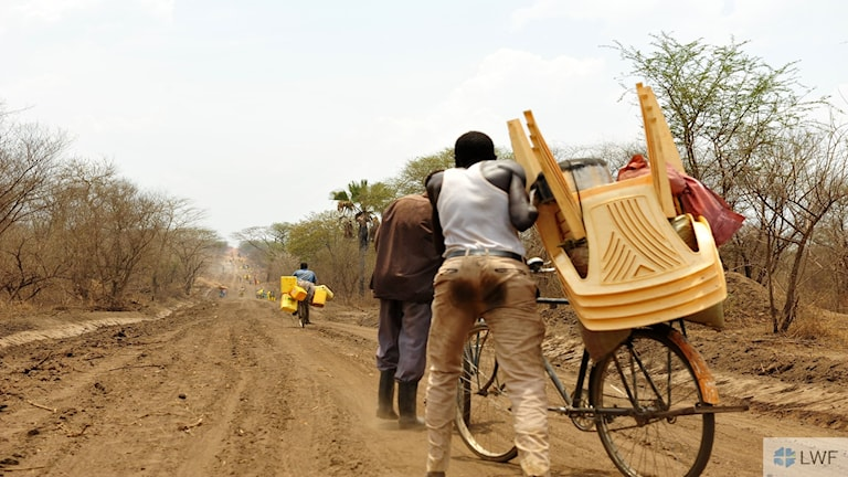 Personer går på en grusväg i ökenlandskap.
