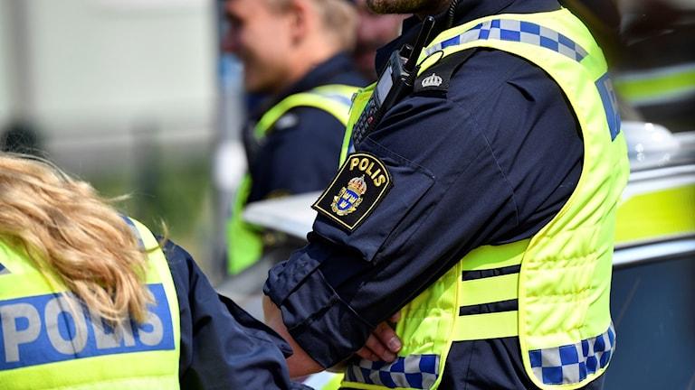 Tre poliser som står utomhus.