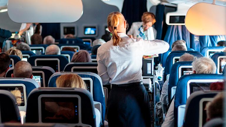 Arkivbild. Flygvärdinna som serverar dryck på ett flygplan.