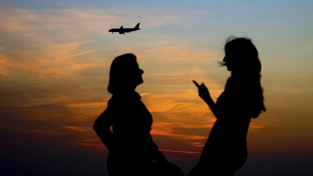 två kvinnor pratar i solnedgången , ett flygplan i bakgrunden