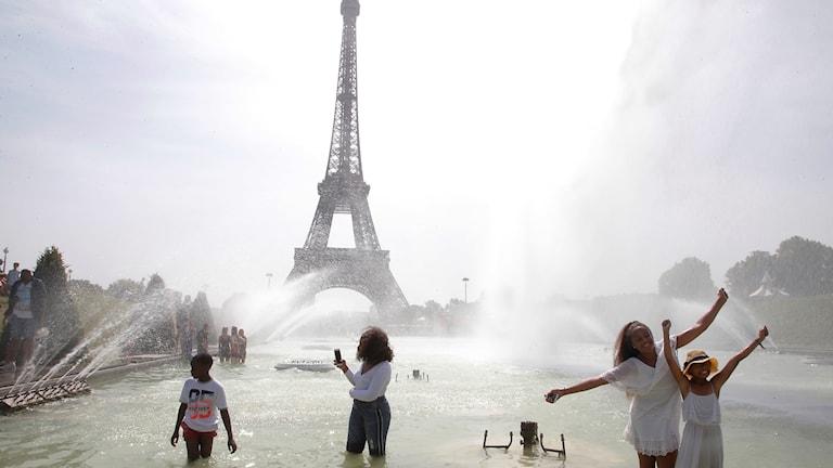 Badande i en fontän framför Eiffeltornet i Paris.