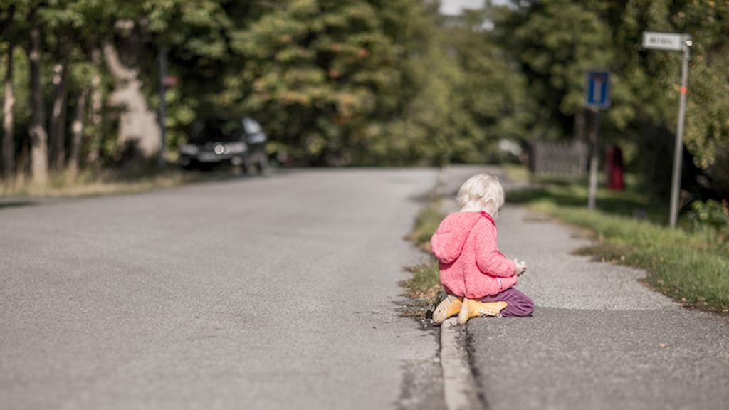 En liten flicka sitter på en trottoar.