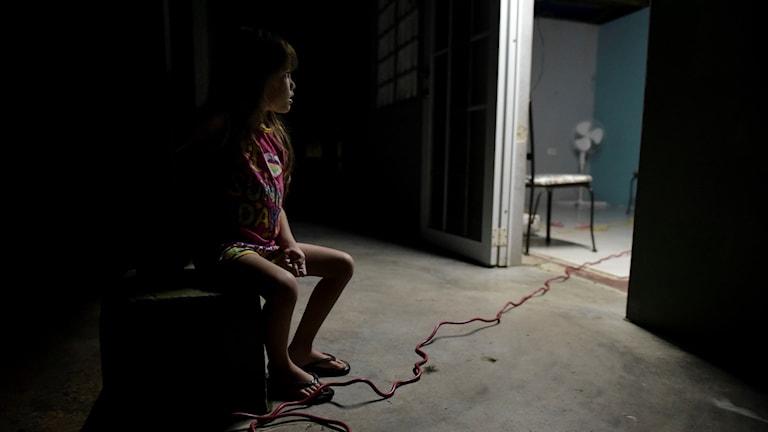 En lite flicka sitter på balkongen och tittar in i sitt hem, som förlorade taket under orkanen Maria. Familjen har ännu inte fått tillbaka elen.