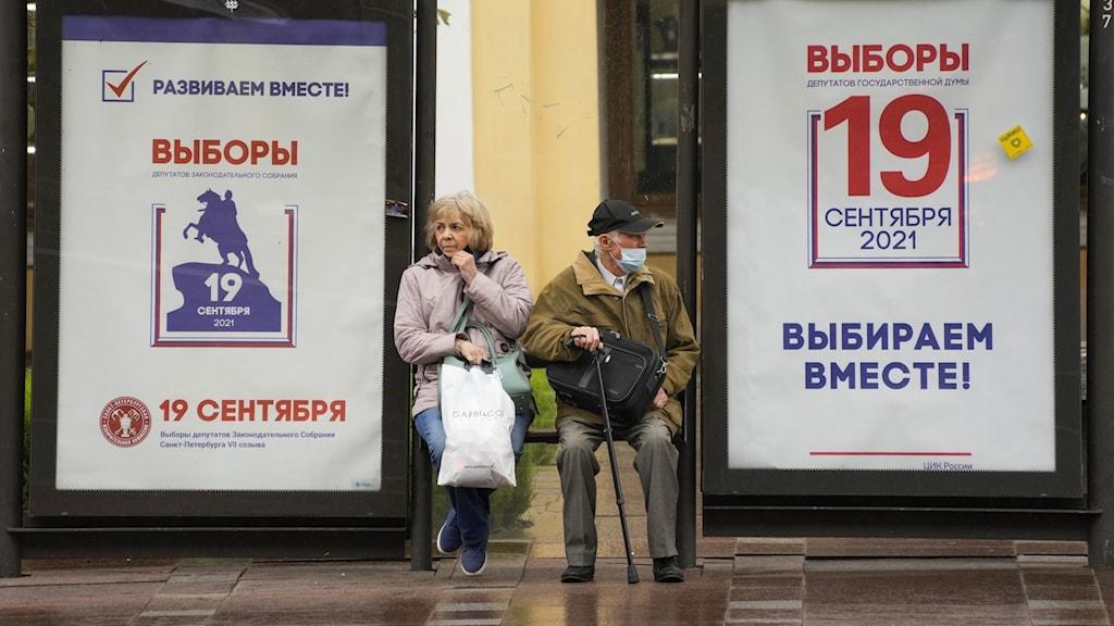 Äldre man och kvinna sitter vid busshållplats där två valaffischer på ryska täcker kuren.