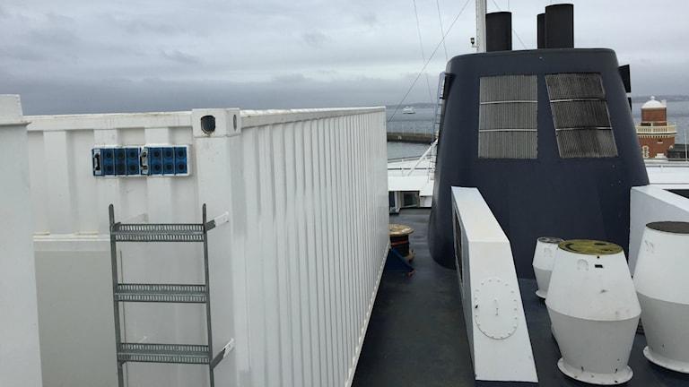 Bilden visar en av de vita containrar där man ska montera batterier som ska driva färjan Aurora. Containern står till vänster om färjans blå skorsten. Foto: Anna Bubenko/Sveriges Radio.