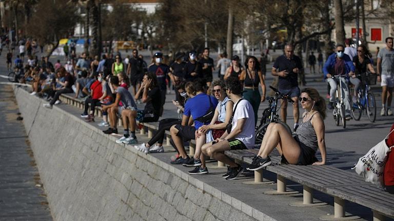 Personer på strandpromenad i Barcelona.