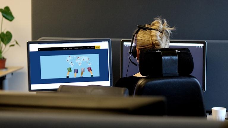 Kvinna med headset i kontorsmiljö, med hemsida på dator.