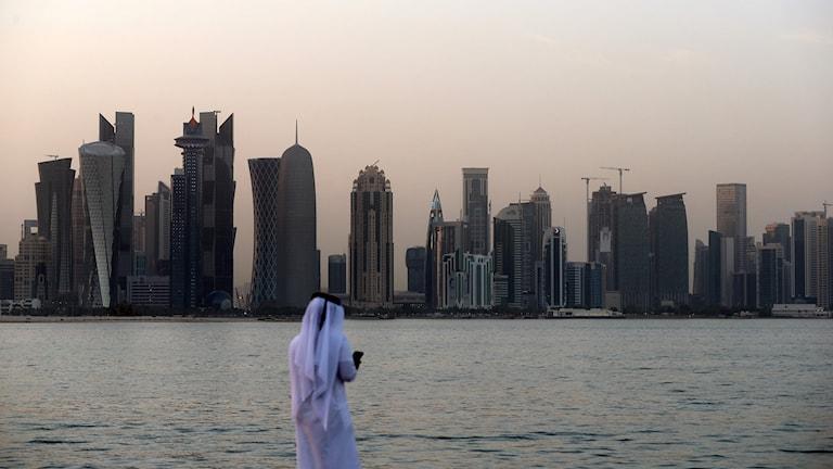 Man framför Qatars huvudstads skyline.