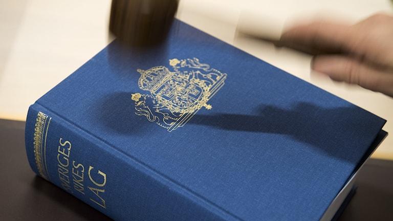 Bild på en lagbok och domarklubba.