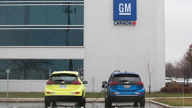 En gul och blå bil framför en vit bilfabrik som det står GM på.