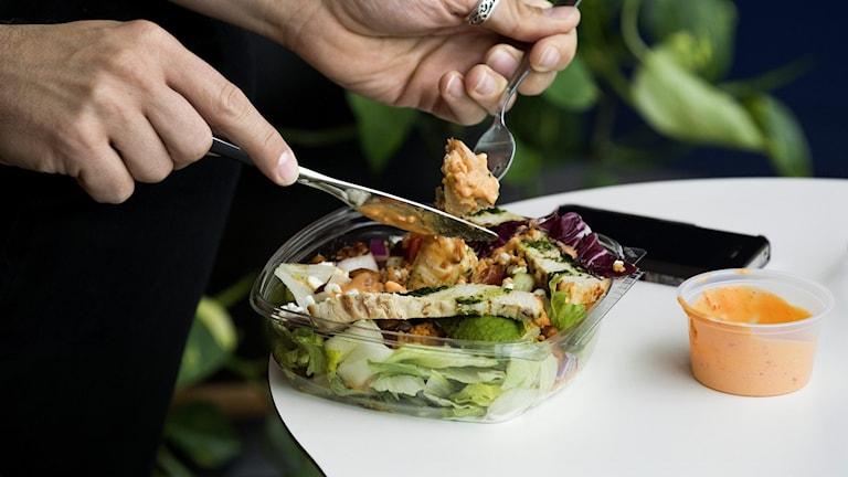 Anonym kvinna äter sallad