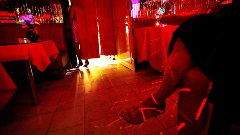 En kvinna går in bakom ett draperi på en bar/nattklubb utomlands.