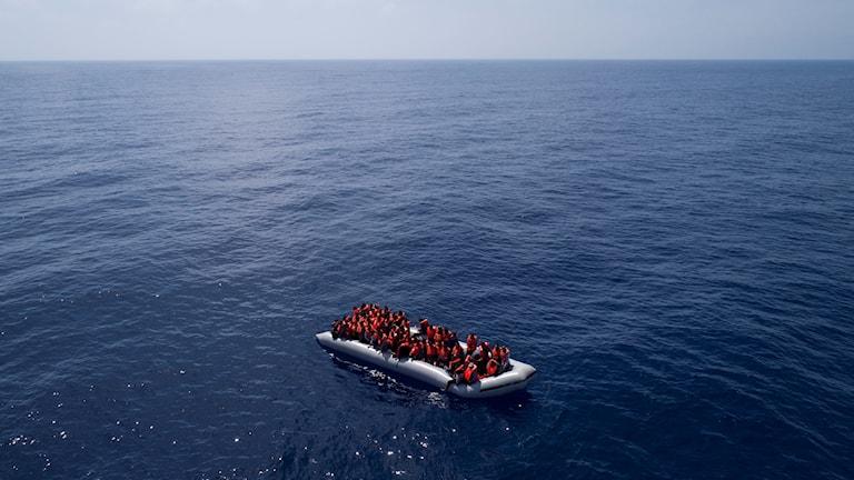 Gummibåt full med människor på ett stort hav..