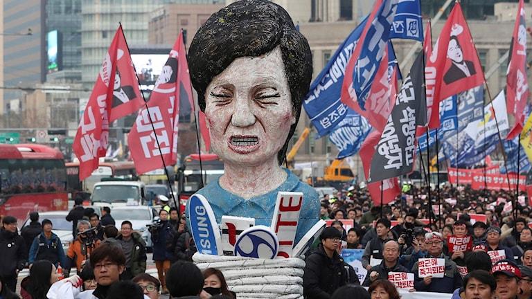 Medlemmar av den koreanska LO bär en avbild av Sydkoreas president Park Geun-Hye