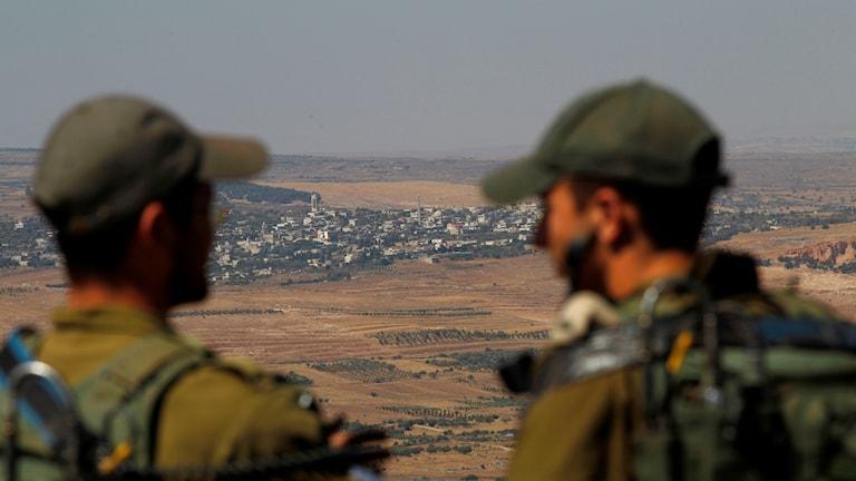 Israeliska soldater i det ockuperade Golanhöjderna blickar in över gränsen mot Syrien.