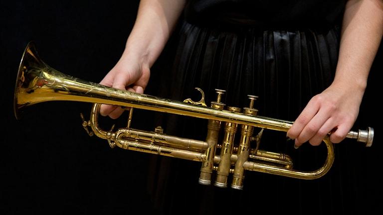 En kvinna håller i en trumpet