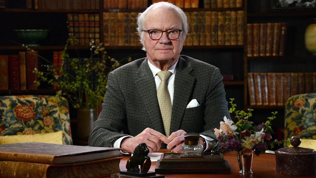 Sveriges kung vid ett skrivbord.