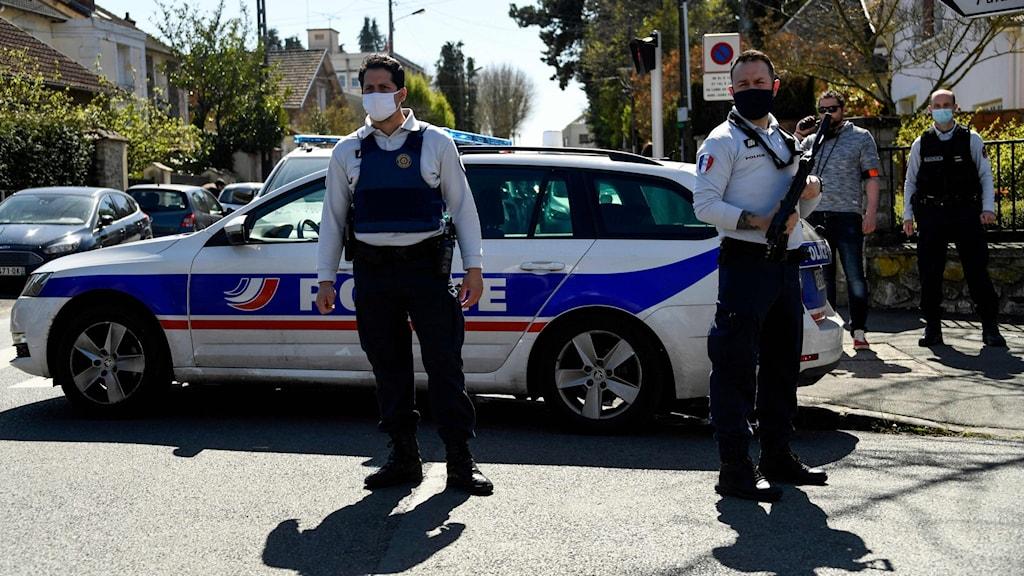 Poliser framför polisbil