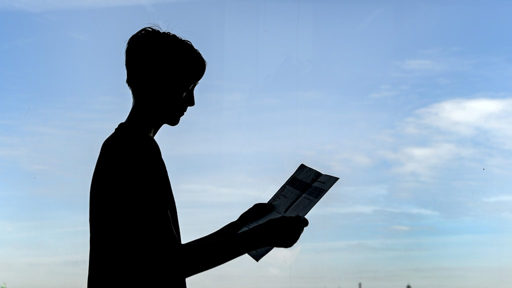 en pojke som håller ett betyg i handen.