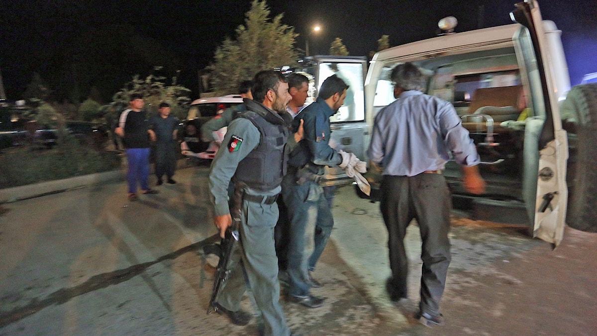 Afghansk polis hjälper en skadad vid attacken mot amerikanska universitetet i Kabul.