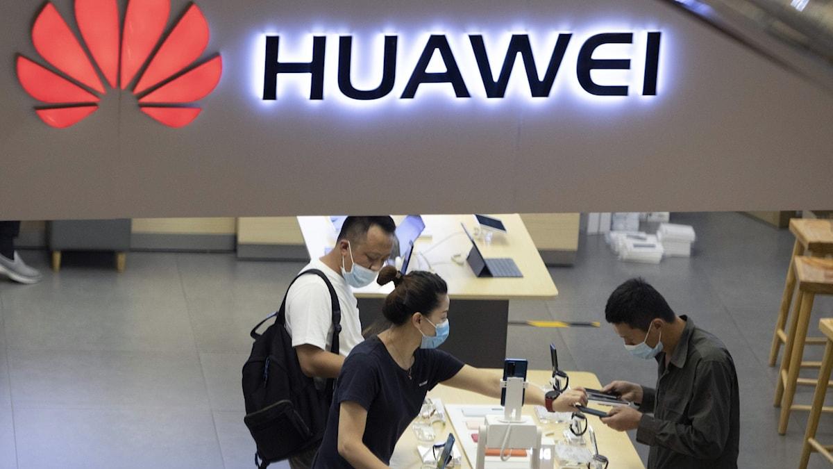 Tre personer med munskydd inne i en Huaweibutik