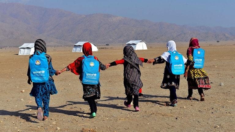 Fem barn med Unicef-ryggsäckar går mot tält i bakgrunden.