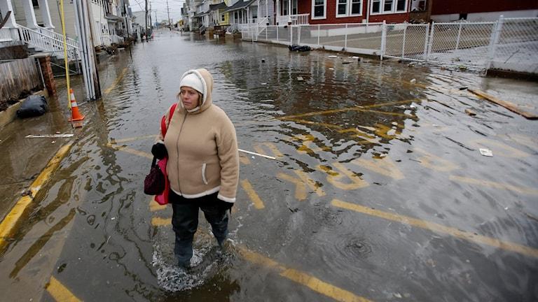 Kvinna går på en gata som är översvämmad med vatten.