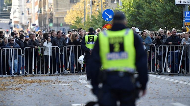 I fokus står en folkmassa bakom kravallstaket och i förgrunden ses ryggen av en polis.