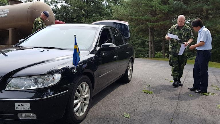 Två män tittar på papper bredvid en bil med en svensk flagga.