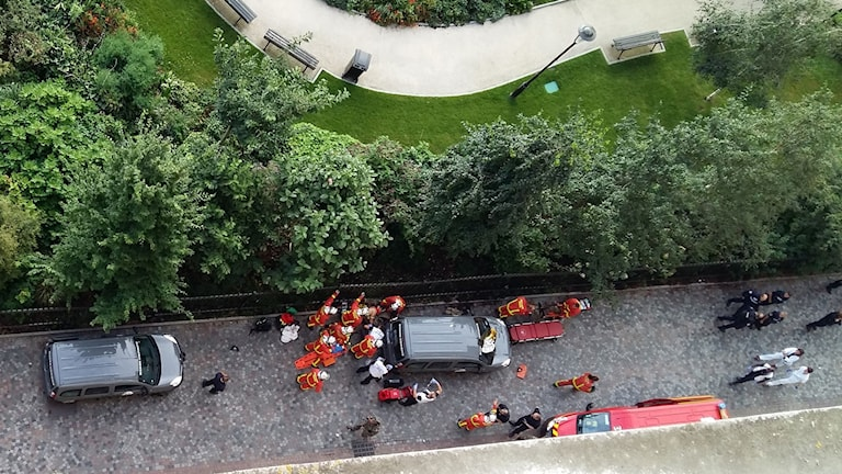 Räddningspersonal står samlade på platsen där en bilist kört in i en grupp soldater.