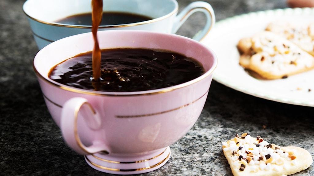 Kaffekopp och ett fat med småkakor, kaffe hälls i koppen.