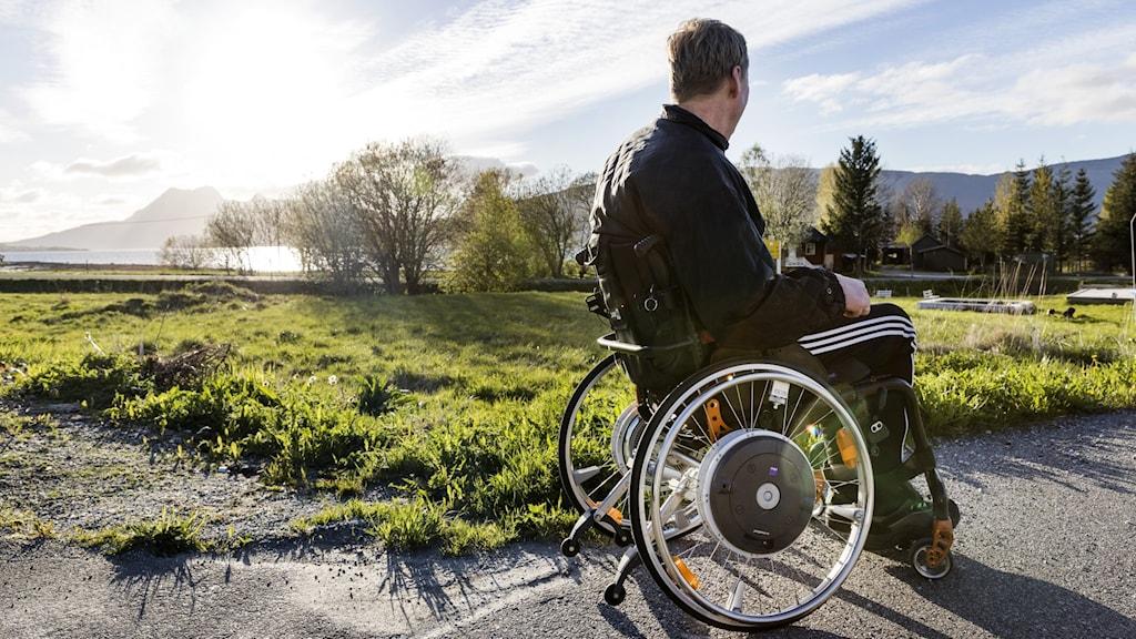 en man som sitter i en rullstol.