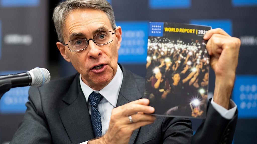 Human RIights Watch chef, Ken Roth, håller upp människorättsorganisationens senaste årsrapport.