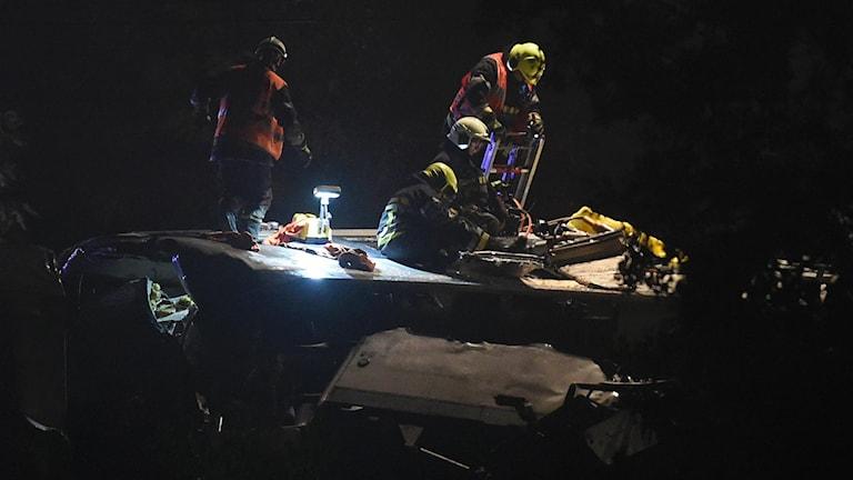 Räddningsarbetare sitter på tågets tak i nattmörker och försöker hjälpa skadade.