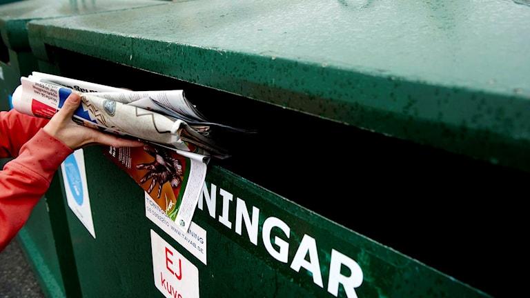 En person stoppar ner tidningar till återvinning.