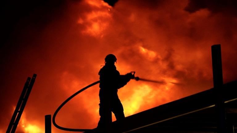 Brandman sprutar vatten på stora lågor.