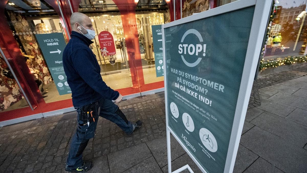 Man medunksydd går förbi en skylt som informerar om coronasymtom på danska.