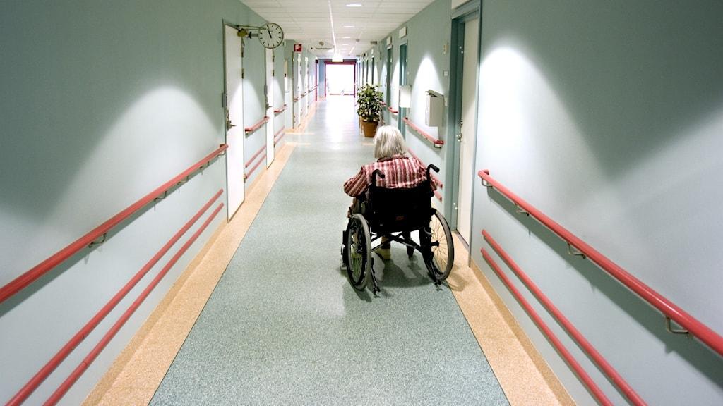 Äldre person i rullstol i korridor